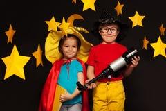 Gulliga ungar som spelar himmeliakttagare med ett teleskop Fotografering för Bildbyråer