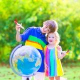Gulliga ungar som spelar med flygplan och jordklotet Arkivfoto