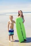 Gulliga ungar som tillsammans spelar på stranden Royaltyfri Bild