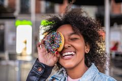 Gulligt ?ta f?r liten flicka Donuts fotografering för bildbyråer