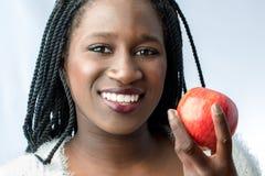 Gulligt afrikanskt tonårigt med det charmiga leendet som rymmer det röda äpplet Royaltyfri Foto