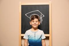 Gulligt anseende för litet barn på svart tavla med det utdragna akademiska locket för krita royaltyfria bilder