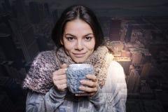 Gulligt anseende för ung kvinna med en kopp te royaltyfri fotografi