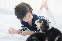 Gulligt asiatiskt barn som spelar med den siberian skrovliga valpen fotografering för bildbyråer