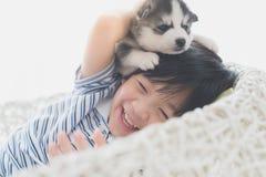Gulligt asiatiskt barn som spelar med den siberian skrovliga valpen arkivfoto