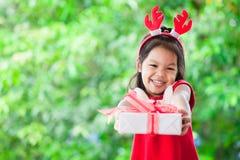 Gulligt asiatiskt barnflickainnehav och ge julgåvan Arkivfoton