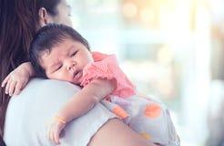 Gulligt asiatiskt nyfött behandla som ett barn flickan som vilar på skuldra för moder` s royaltyfri fotografi