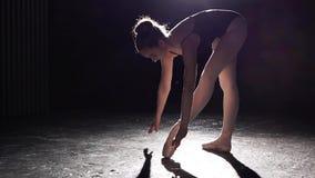 Gulligt böjligt ballerinaanseende på hennes pointebalettskor i strålkastare på svart bakgrund i studio långsam rörelse arkivfilmer