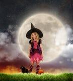 Gulligt barn i allhelgonaaftonhäxadräkt framme av månen royaltyfria bilder