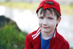 Gulligt barn i rött lock på utomhus- arkivbild