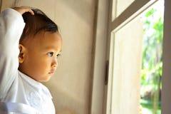 gulligt barn se ut fönstret royaltyfri foto