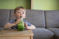 Gulligt barn som dricker en grön smoothie Arkivbilder