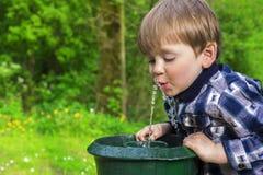 Gulligt barn som dricker från en springbrunn Royaltyfri Foto