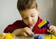 Gulligt barn som spelar med plasticine Arkivfoto