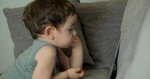 Gulligt barn som underhåller med minnestavlan Little Boy som spenderar fritid som spelar den mobila leken i och, krossar det ljus arkivfilmer