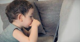 Gulligt barn som underhåller med minnestavlan Little Boy som spenderar fritid som spelar den mobila leken i och, krossar det ljus stock video