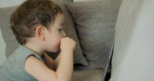 Gulligt barn som underh?ller med minnestavlan Little Boy som spenderar fritid som spelar den mobila leken i och, krossar det ljus stock video