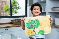 Gulligt barn som visar en teckning arkivfoton