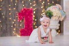 Gulligt behandla som ett barn årigt sammanträde för flicka 1-2 på golv med rosa ballonger i rum över vit isolerat caken för födel royaltyfri foto