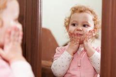 Gulligt behandla som ett barn applicera kräm på henne kinder arkivfoto