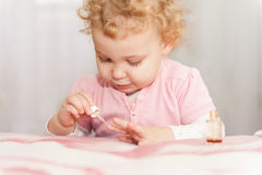 Gulligt behandla som ett barn att leka med fostrar manicureskönhetsmedel royaltyfri bild