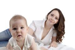 Gulligt behandla som ett barn att posera på kameran och hennes mamma på bakgrunden Arkivbild