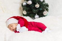Gulligt behandla som ett barn att sova i julkläder Royaltyfri Fotografi