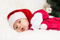 Gulligt behandla som ett barn att sova i julkläder Arkivfoton