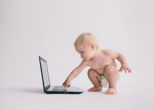 Gulligt behandla som ett barn att spela med en bärbar datordator som isoleras på vit Arkivbilder