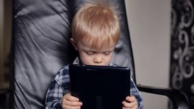 Gulligt behandla som ett barn att spela på en minnestavla i läderfåtölj arkivfilmer