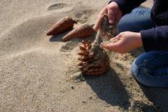 Gulligt behandla som ett barn barnflickahänder som spelar med sand på den soliga stranden arkivbilder