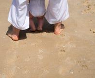 Gulligt behandla som ett barn benet för ` s i sanden arkivbilder