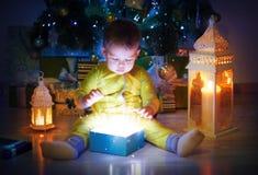Gulligt behandla som ett barn den öppnade magiska gåvaasken under Xmas-träd royaltyfria foton