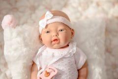 Gulligt behandla som ett barn - dockan i vit blek kläder på beige bakgrund royaltyfria foton
