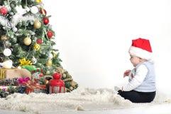 Gulligt behandla som ett barn en årspojke som spelar med julgrangarnering Royaltyfria Foton
