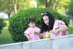 Gulligt behandla som ett barn flickalekbollar med modern Arkivfoto