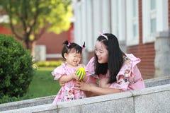 Gulligt behandla som ett barn flickalekbollar med modern Arkivbild