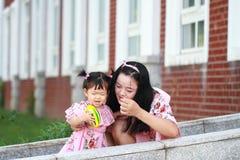 Gulligt behandla som ett barn flickalekbollar med modern Royaltyfri Foto