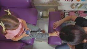 Gulligt behandla som ett barn flickan som använder den smarta telefonen på pedikyrtillvägagångssättet på skönhetbrunnsortsalongen stock video