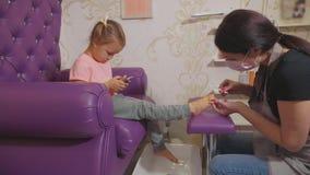 Gulligt behandla som ett barn flickan som använder den smarta telefonen på pedikyrtillvägagångssättet på skönhetbrunnsortsalongen lager videofilmer