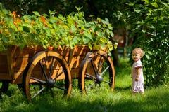 Gulligt behandla som ett barn flickan bredvid en dekorativ blommavagn Fotografering för Bildbyråer