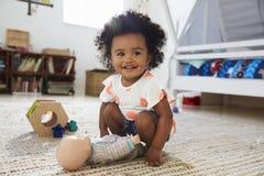 Gulligt behandla som ett barn flickan som har gyckel i lekrum med leksaker arkivfoton