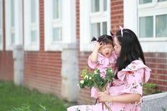 Gulligt behandla som ett barn flickan har gyckel med modern Fotografering för Bildbyråer