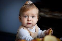 Gulligt behandla som ett barn flickan med en hatt på hennes huvudblickar in i kameran royaltyfria bilder