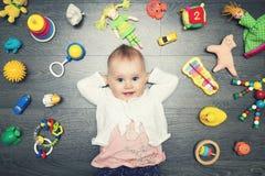 Gulligt behandla som ett barn flickan med lotten av leksaker på golvet Top beskådar Royaltyfri Foto