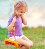 Gulligt behandla som ett barn flickan på gungan Royaltyfri Fotografi