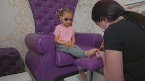 Gulligt behandla som ett barn flickan på pedikyrtillvägagångssättet i skönhetbrunnsortsalong arkivfilmer