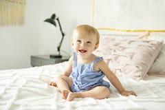 Gulligt behandla som ett barn flickan på säng hemma arkivbilder