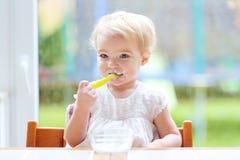 Gulligt behandla som ett barn flickan som äter yoghurt från skeden Fotografering för Bildbyråer