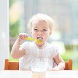 Gulligt behandla som ett barn flickan som äter yoghurt från skeden Arkivfoto